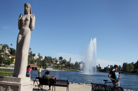 """The statue known as the Lady of the Lake is actually titled """"Nuestra Reina de Los Angeles."""" She stands watch as visitors return to the newly renovated park."""