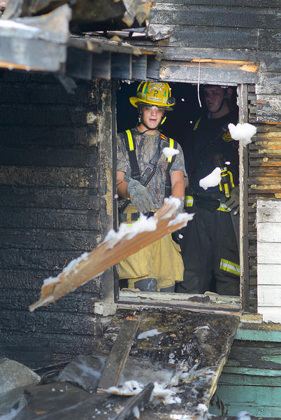 Firefighter Thomas Cleveland, with the Williamsport Volunteer Fire & EMS Co. 2, throws burnt debris out of the window of a house at 20 N. Artizan St. in Williamsport Wednesday evening.