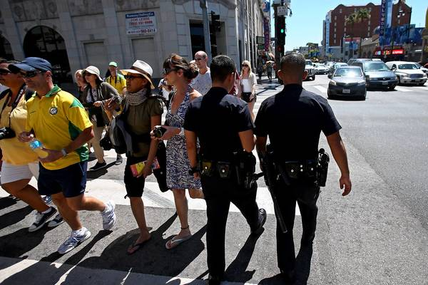 Police patrol at Hollywood Boulevard and Highland Avenue on Wednesday. A 'flash mob' of youths rampaged through the area Tuesday night, stealing from pedestrians and shops.
