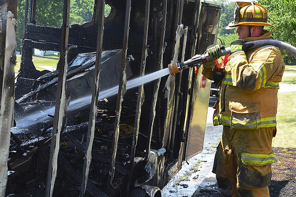 Hagerstown Fire Department's Shawn Wieczorek hoses off the remains of a trailer and lawn care equipment that burned Wednesday on Sweeney Drive. A 37-year-old man was flown to The Johns Hopkins Burn Center in Baltimore Wednesday afternoon after he suffered burns.