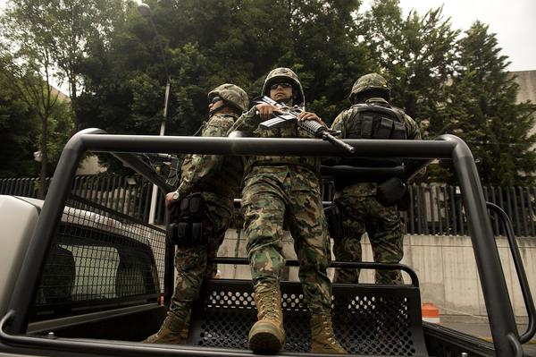 Mexican marines patrol near the Deputy Attorney Specialized in Investigation of Organized Crime (SEIDO) headquarters in Mexico City after the arrest of Zetas gang leader Miguel Angel Trevino Morales.