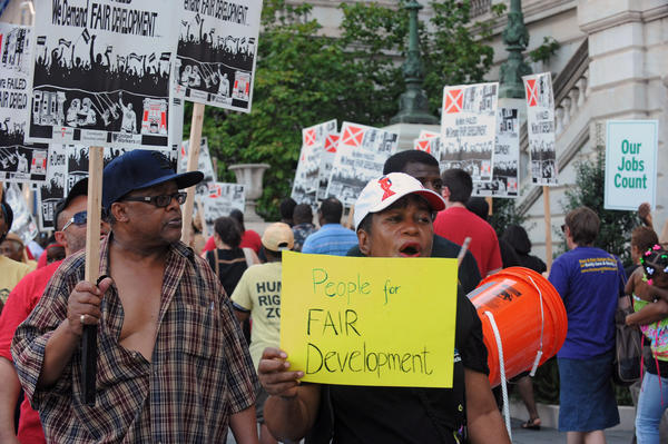 Pearl Davis, center, joins about 100 other people gathered in front of Baltimore City Hall to protest against the proposed $107 million tax increment financing (TIF) deal for the developer of the upscale Harbor Point. The City Council held a hearing on the TIF deal after the protest.