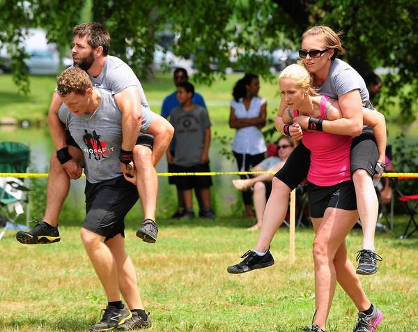 Cross Fit Aspire team members Michael Ferguson of Cherry Hill (left) carries Justin McGinley of Cherry Hill as team mates Jill Ferguson of Cherry Hill, NJ (right) carries Beth Walker of Mt Laurel, NJ during cross fit competition in 2012.