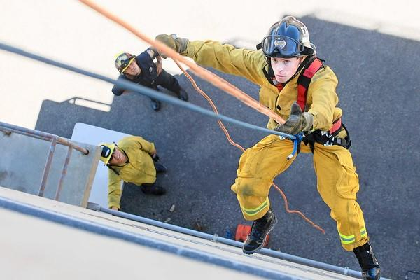 Orange County Fire Authority Explorer Josh Salaets, 17, rappels down one side of a fire tower during training exercises on Urban Search and Rescue at Costa Mesa Fire Station 4 on Wednesday. OCFA firefighter Jordan Smith, top left, and Kern County firefighter Eddie Lee, bottom left, look on from below.