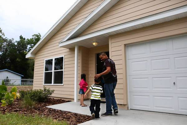 Hailey Partida, 7, left, Luis Gonzalez-Berrios, 4, and Jose Gonzalez-Berrios enter their new Habitat for Humanity of Lake-Sumter house on Friday, July 12, 2013.