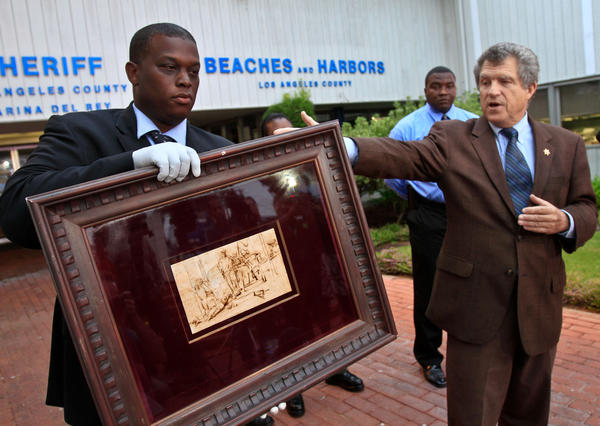 Los Angeles County Sheriff's Department spokesman Steve Whitmore, right, at a 2011 news conference where Deputy Clarence Williams shows off a Rembrandt etching that had been recovered after being stolen.