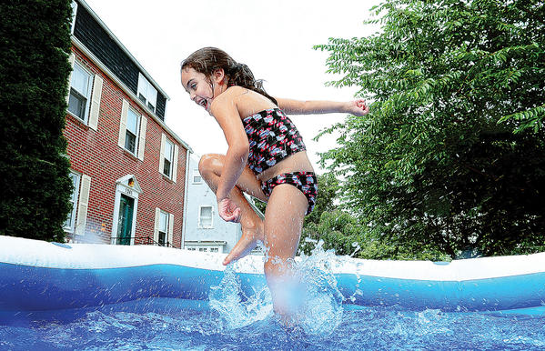 Sicilly Sellars, 5, splashes around in an inflatable pool outside her Potomac Ave home in Hagerstown on Thursday afternoon.