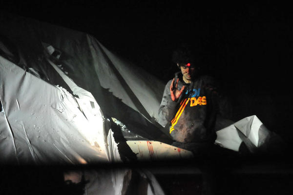 The laser of a sniper's rifle is trained on Dzhokhar Tsarnaev as he surrenders from a boat in a backyard. To read the story and see the rest of the photos, visit http://www.bostonmagazine.com/news/blog/2013/07/18/tsarnaev/