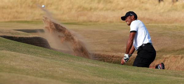 Tiger Woods plays a shot out of the bunker at the 11th during the first round of the British Open at Muirfield golf course.