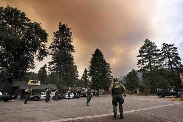 Sheriff's deputies keep watch in the mountain retreat of Idyllwild south of Palm Springs as the Mountain fire rages in the distance. Most residents left when an evacuation was ordered.