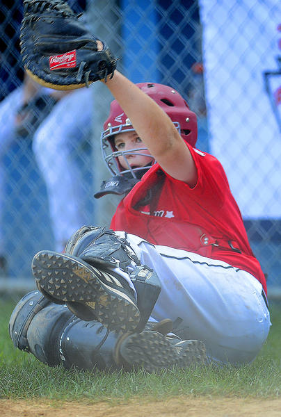 West Salisbury catcher Blake Corbin holds up his glove after making the third out in the top of the second inning of Thursday's Maryland 10-11 Little League Tournament championship game against Elkton.