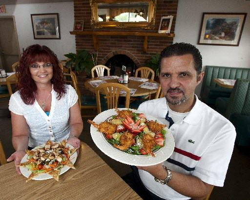 Owner John Pittas with manager Dawn Russek at the Schnecksville Diner holding dishes of Greek salad with chicken (left) and tropical island salad.