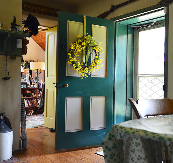 A brightly colored door opens the way to a small kitchen.