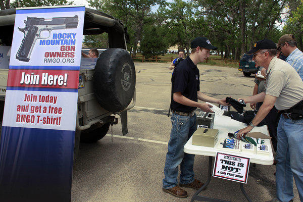 Seth Walters, a staffer for the gun rights group Rocky Mountain Gun Owners, hands out promotional T-shirts before a gun rights rally held Friday. Nearby, a Mayors Against Illegal Guns remembrance event was held honoring the victims of the Aurora theater shootings and advocating gun control.