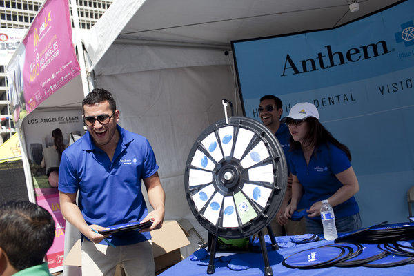 An Anthem Blue Cross executive hands out prizes to participants spinning the wheel at the company's booth at the Fiesta Broadway event in downtown Los Angeles in April. Although the company plans to offer individual health policies through California's new insurance exchange, it says it won't offer coverage there to small businesses.
