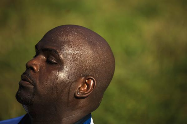 A man sweats as he stretches after a workout during a hot day in New York, July 16, 2013.