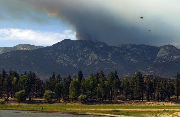 A plume of smoke looms over Lake Hemet as a water-dropping helicopter heads to the lake to refill.