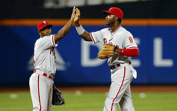 NEW YORK, NY - JULY 19: Domonic Brown #9 and Jimmy Rollins #11 of the Philadelphia Phillies celebrate after defeating the New York Mets at Citi Field on July 19, 2013 in the Flushing neighborhood of the Queens borough of New York City.