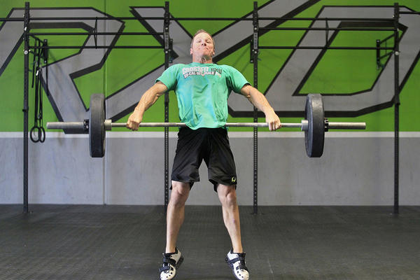 Owner Bryan Wadkins demonstrates how to do a squat and snatch, as part of a CrossFit exercise routine known as Amanda, at his gym CrossFit RXD in Anaheim on Monday. Wadkins is heading to the Olympic Games to compete in CrossFit. He was ranked as one of the fittest out of 5,000 men in his category.