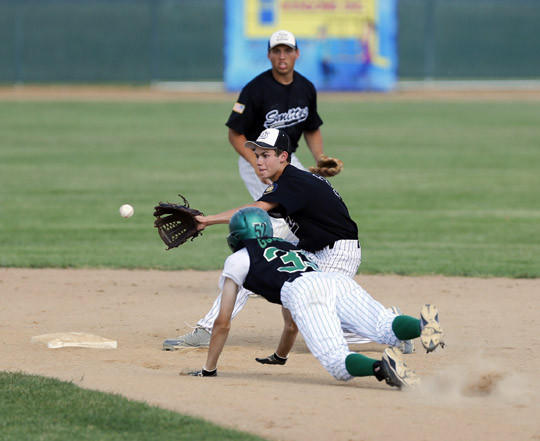 Trey Vilhauer of the Aberdeen Smittys, center, reaches for the ball as Pierre's Ryan Goodwin starts his slide into second base during Tuesday's game at Fossum Field. Backing up the play for the Smittys is Lucas Lorenz. photo by john davis taken 7/2/2013