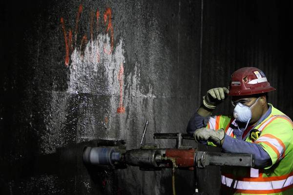 A worker takes core samples of concrete compromised by the July 13 fire in a tunnel underneath the 5 Freeway. Intense heat makes water molecules in the cement evaporate, causing cracks.