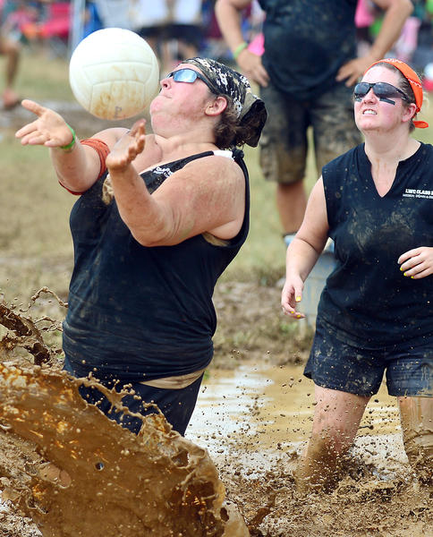 Swats Team captin Jennifer Swatsworth, left, and Amy Gyurisim both of Hagerstown play in the 2013 MUDD Volleyball Tournament Saturday in Hagerstown benefiting the Community Free Clinic.