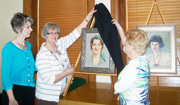Two oil paintings by Frank C. Ashford are shown at a recent meeting of the Yellow Brick Road Questers of Aberdeen. The painting being unveiled is Portrait of a Young Woman, which was recently restored. At right is a painting discovered during the restoration of Portrait of a Young Woman. From left are Dacotah Prairie Museum director Sue Gates and Evelyn Nikolas and Jean Weber of the Yellow Brick Road Questers.
