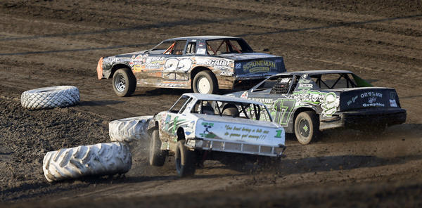 Arthur Berger, of Ortley (22) leads Tyler Lambert, of Aberdeen (17) as Jodie Michaelsohn, of Aberdeen (1M) clips a tire as the trio goes through turn one in the second heat of Street Stock action Friday night at the Brown County Speedway. photo by john davis taken 7/19/2013