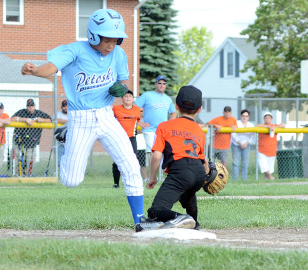 Petoskey's Jarrin Kelly (left) beats a throw for an infield hit against Cheboygan during a District 13 Little League Minors Division (ages 9-10) championship game Friday in Cheboygan. Cheboygan won the district title with an 11-3 win.