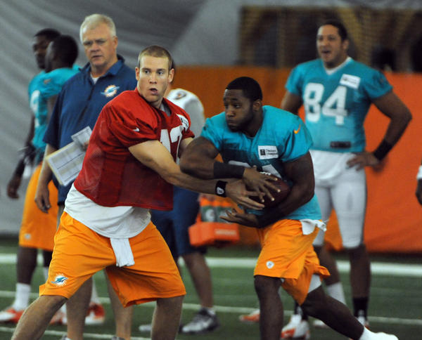 Ryan Tannehill hands off to Marcus Thigpin during training camp, Monday, July 22, 2013, at Nova Southeastern University in Davie.
