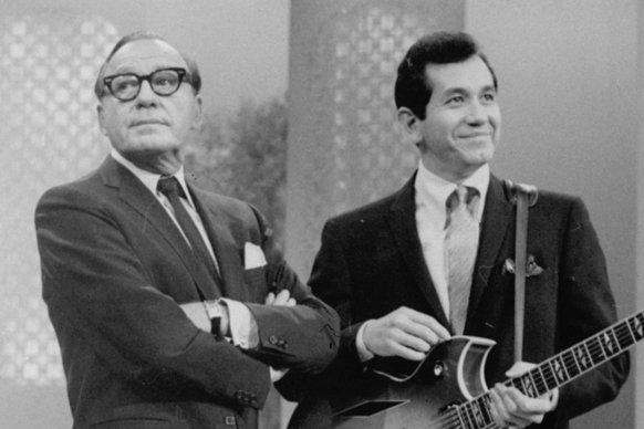"Comedian Jack Benny was known as a master of comic timing. This was the expression that accompanied his famous ""Hmm¿m¿m."" Here he's inflicting it on singer¿guitarist Trini Lopez in November 1966."