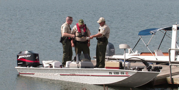 Officers of the Pennsylvania Waterways Commission examine the boat of the man who water rescue crews are searching for at Beltzville Lake on Monday.