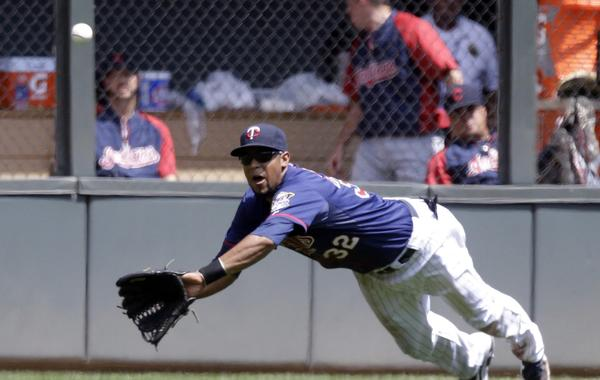 Minnesota Twins outfielder Aaron Hicks dives to make a catch against the Cleveland Indians on Sunday. The former Long Beach Wilson High star is working hard to make his major league dreams a reality.
