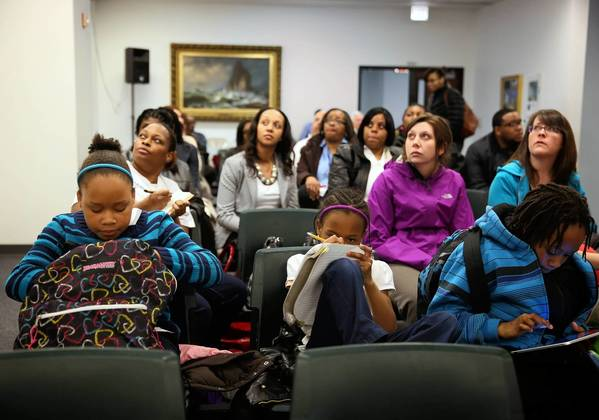 Students do their homework during a public hearing on the proposal to close Dumas Technology Academy and consolidate the school with Wadsworth Elementary. The hearing was held at Chicago Public Schools headquarters.
