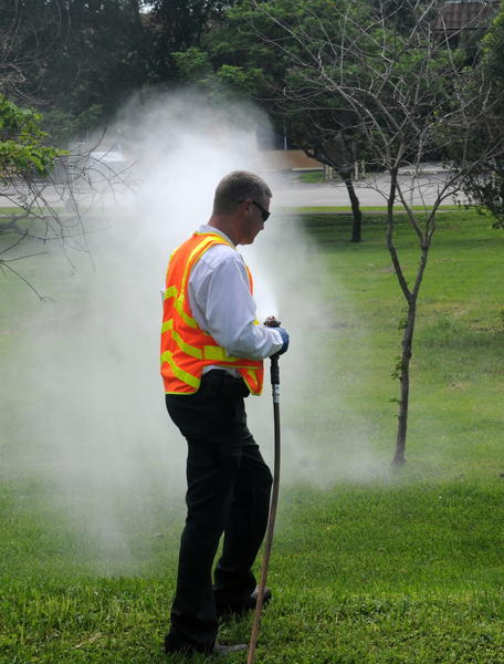 Broward County Mosquito Control Inspector Eric Fusco sprays larvicide onto a field on the northwest corner of Stirling Road and 56th Avenue on Monday after heavy rain left pools of water. (Taimy Alvarez, Sun Sentinel)