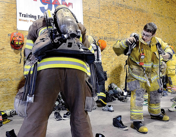 Devin Dick of South Mountain, Pa. puts on his firefighting gear for a training excercise at the eighth annual Franklin County Fire Chiefs Association Junior Firefighter Academy.
