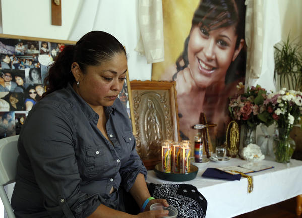 Celene Castillo sits in front of a photo of her 18-year-old niece, Kassandra Castillo, at the family's home in Franklin Park.