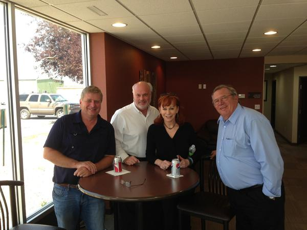 From left, Darrell Hillestad, Jeff Catron, Reba McEntire and Gary Dahlerup posed for a quick picture Friday afternoon. The three men are pilots and got to meet McEntire when her jet stopped in Aberdeen to refuel.