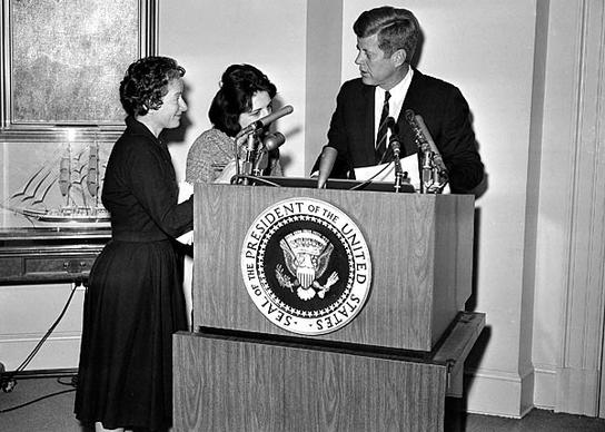 Correspondents Helen Thomas, center, of UPI and Frances Lewine of the Associated Press ask President Kennedy for copies of his announcement pledging federal help to quell rioting in Birmingham, Ala., in 1963. Thomas went to the White House at a time when female reporters were largely expected to write about the first lady's social calendar, fashion and manners.