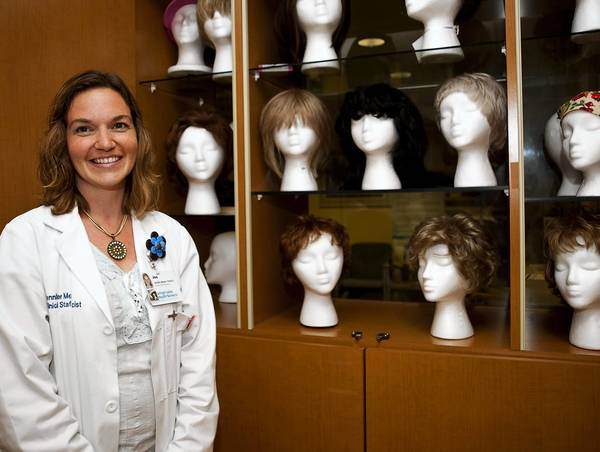 Lehigh Valley Hospital Pharmacist Jennifer Mesker poses with wigs for cancer patients, Jennifer recently donated 12 inches of her hair to Locks of Love after being moved by story of a patient at the Cancer Center of Lehigh Valley Hospital-Cedar Crest.