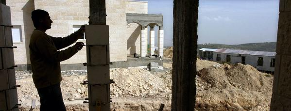 In this file photo from March 8, 2005, a worker builds a new structure in the illegal outpost of Amona in the central West Bank. To satisfy a court order, settlers began tearing up an access road to the settlement on Tuesday.
