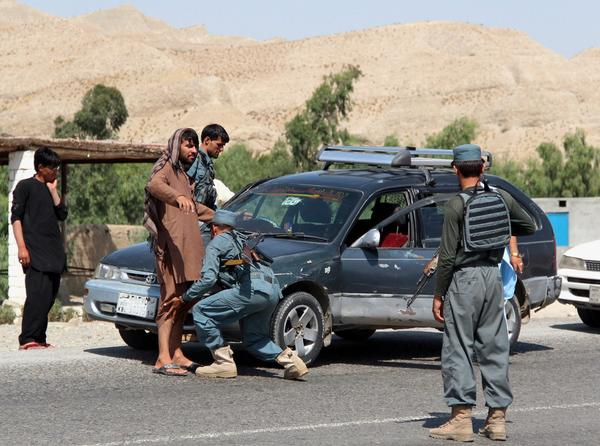 Afghan policemen frisk drivers at a checkpoint in Nangarhar on Tuesday amid stepped-up security after three NATO soldiers were killed in a suicide bomb blast in Wardak province.
