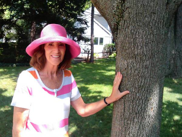 "Susan Gatto, of Wilmette, stands next to the maple tree in the parkway in front of her home. ""Wilmette is very dedicated to its trees,"" she said."