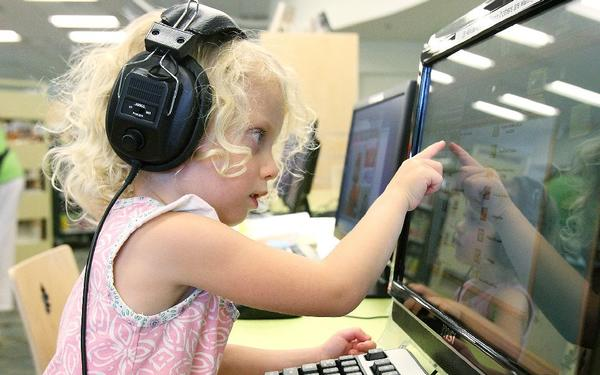 Kenley Miller, 4, of Burbank, points to what she heard in the earphones on a children's computer at the Northeast branch library on the day of reopening Monday after an extensive remodel.
