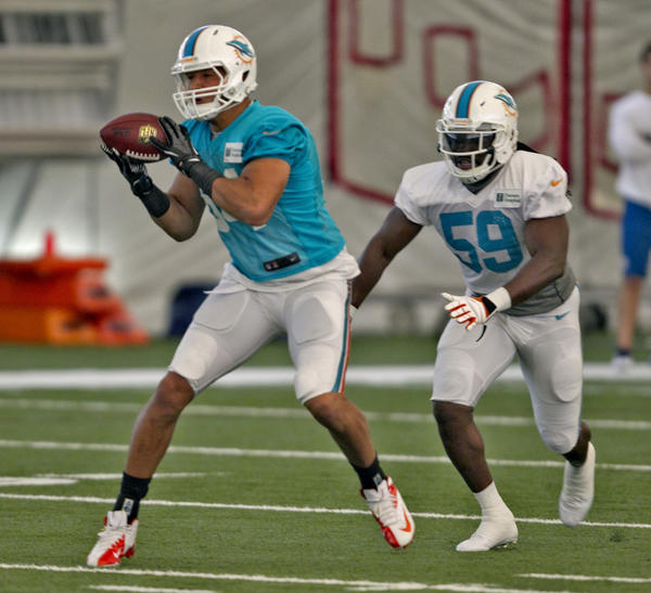 Tight end Michael Egnew catches a pass in front of Dannell Elelerbe at Miami Dolphins practice at the Dolphins training facility at NSU in Davie on July 23rd,2013.