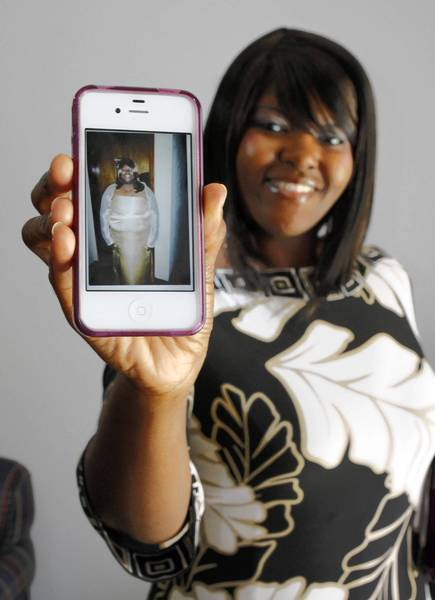Lasheka Mack, of Orlando, holds her smartphone showing a picture of her before losing 88 pounds through prayer.