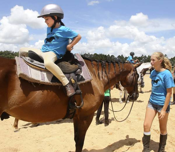 Six-year-old Morgan Allen plays a game with her instructor Sophia Beecham in which the rider turns around in their saddle. DreamCatcher Horse Ranch is having its 4th summer camp at their facility north of Clermont.