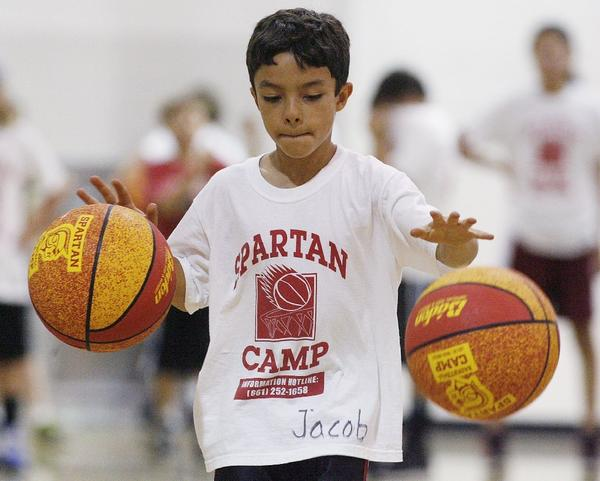 Jacob Koch, 7, of Los Angeles, dribbles two basketballs at the annual Spartan Basketball Camp with La Canada High School hoops coach Tom Hofman at the school gym on July 10. (Tim Berger/Staff Photographer)