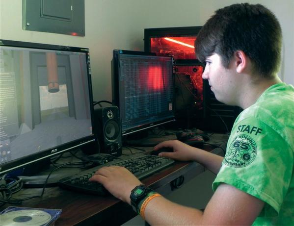Joel Horne of Waynesboro, Pa., designs a flight simulator in the new computer building - formerly a dilapidated health building - at Camp Sinoquipe.