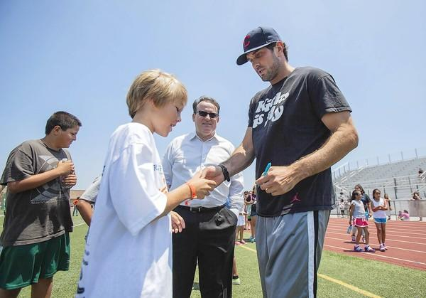 Former USC football quarterback and NFL quarterback Matt Leinart signs an autograph for Jackson Galitski, 11, at the Costa Mesa Summer Sports Camp at Estancia High School on Tuesday.
